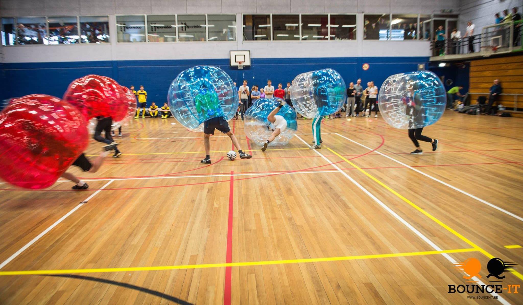 Dit is een foto met mensen die bubble voetbal spelen in een sporthal